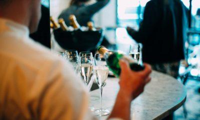 mężczyzna noszący koszule, rozlewa szampana do kieliszków z butelki