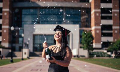 Szczęśliwa kobieta trzyma butelkę szampana, która rozpryska w powietrze.