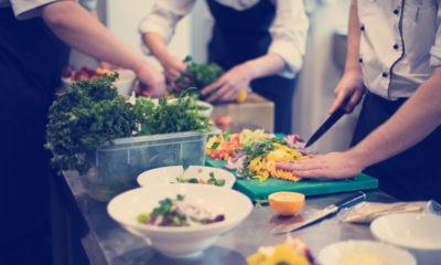 Trójka kucharzy gotują na kuchni jedzenie