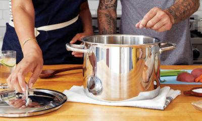 Dwójka osób gotuje potrawę na kuchni